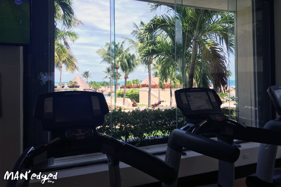 A gym view from treadmills looking out onto beach