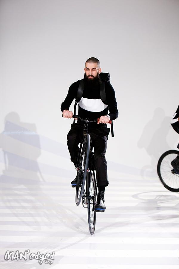 A model popping a wheelie at Uri Minkoff's men's fashion presentation.