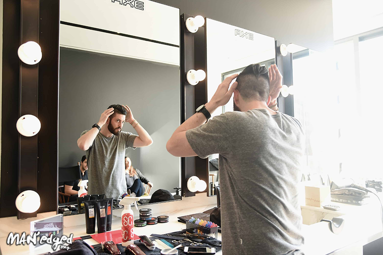 Guy in mirror styling hair, men's hair style