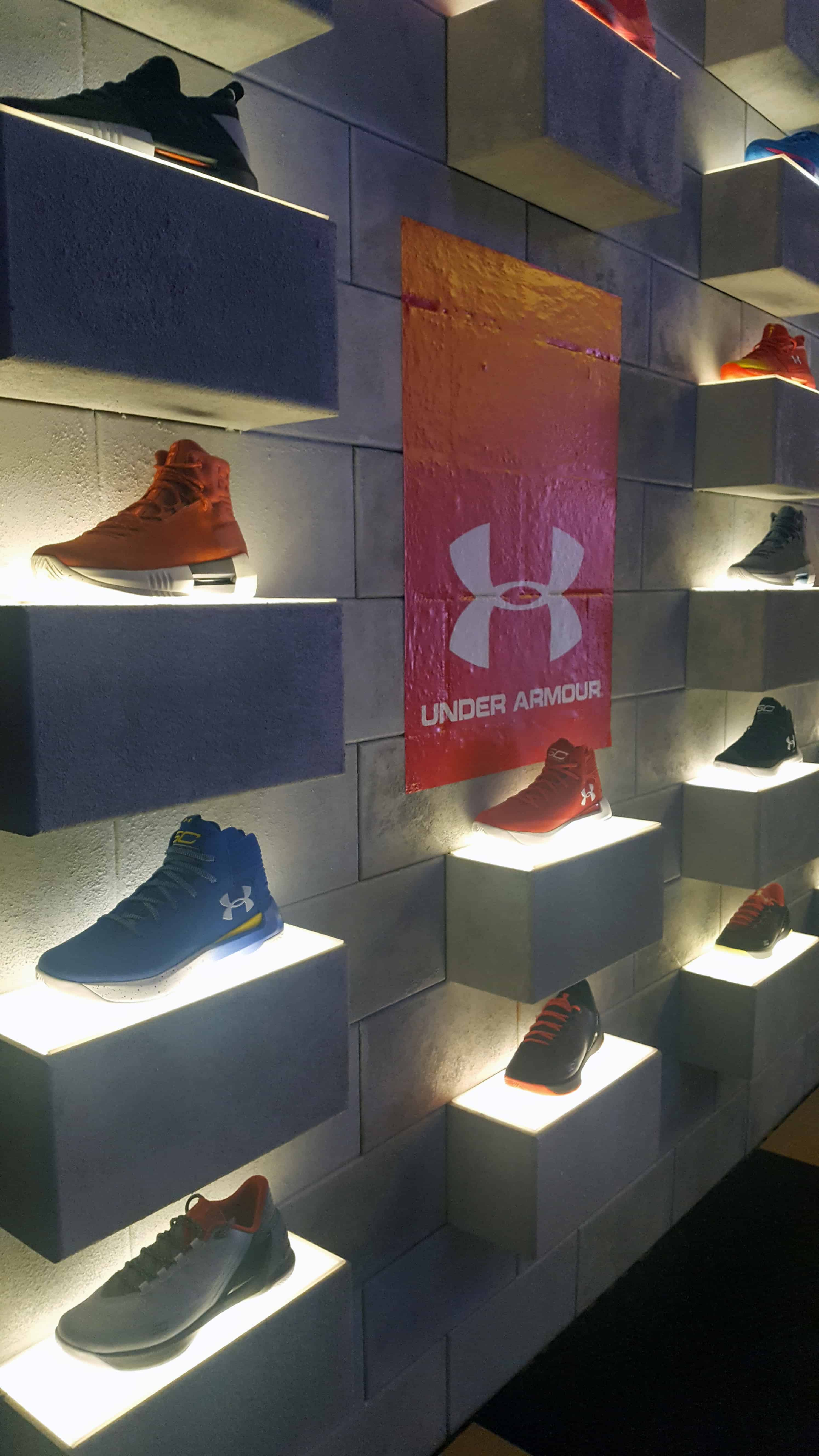 Under Armour sneakers displayed on wall