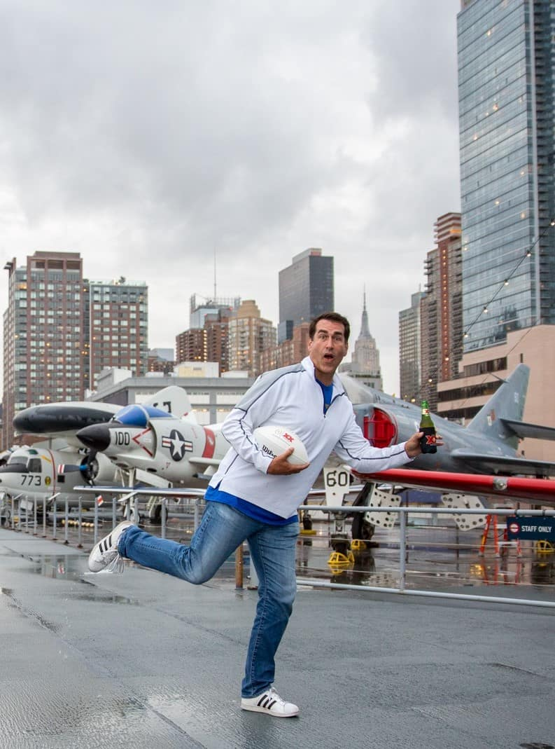Ron Riggle with Dos Equis search for best college football fan standing on the Intrepid NYC
