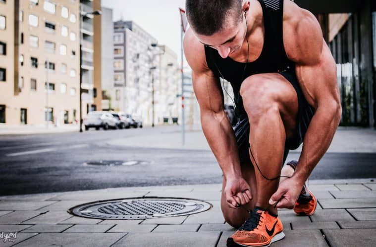 athletic Guy tying shoe during run in TCS NYC Marathon