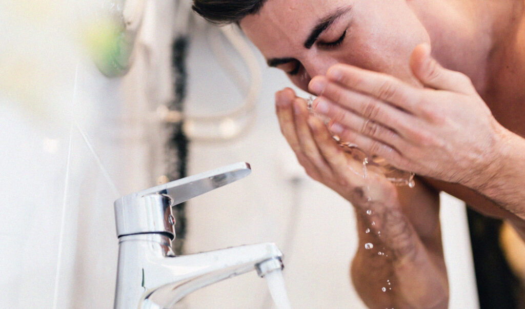 man washing face in his skincare regime
