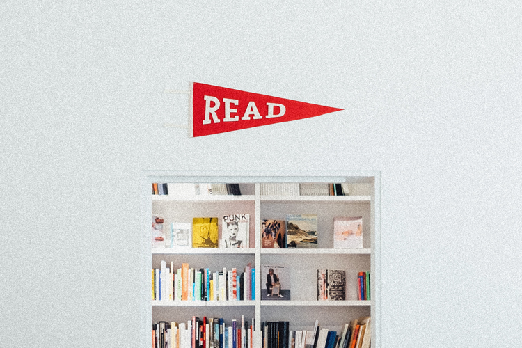 a sign above a filled book shelf that says read