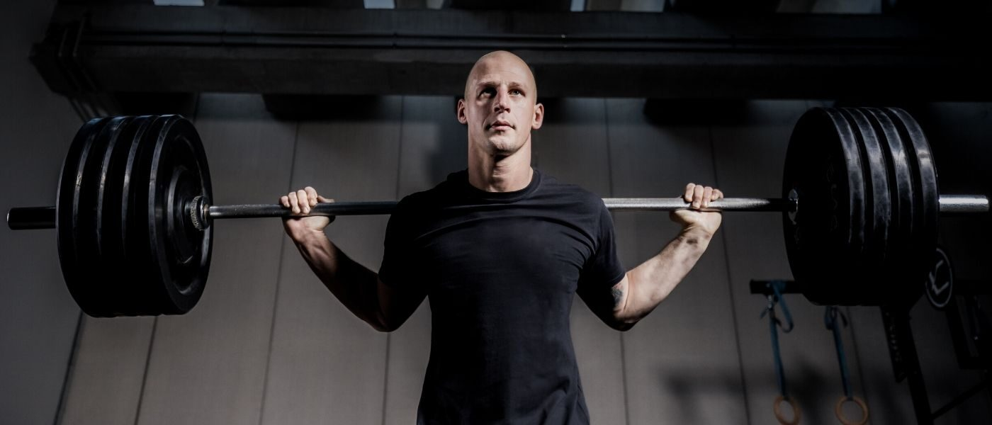A man standing with a bar with weights over his shoulders.
